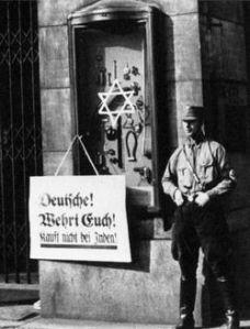 """No ano de 1933, foi realizado um boicote em todos os comércios de judeus na Alemanha. Neste cartaz fixado em um comercio judeu afirma: """"Alemães defendam se! Não comprem dos judeus!"""""""